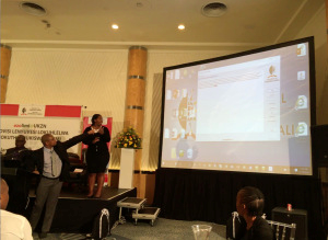 Langa Khumalo, ULPDO director, giving the spellchecker demo, pointing out a detected spelling error in the text. On his left, Mpho Monareng, CEO of PanSALB.